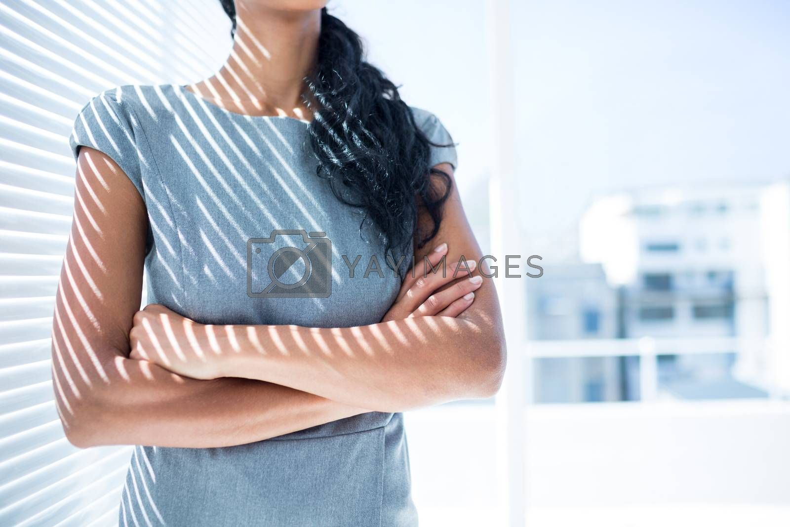 Royalty free image of Businesswoman with arms folded in the office by Wavebreakmedia