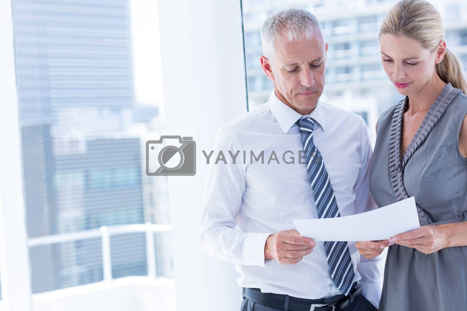 Royalty free image of Business people talking over a paper sheet by Wavebreakmedia