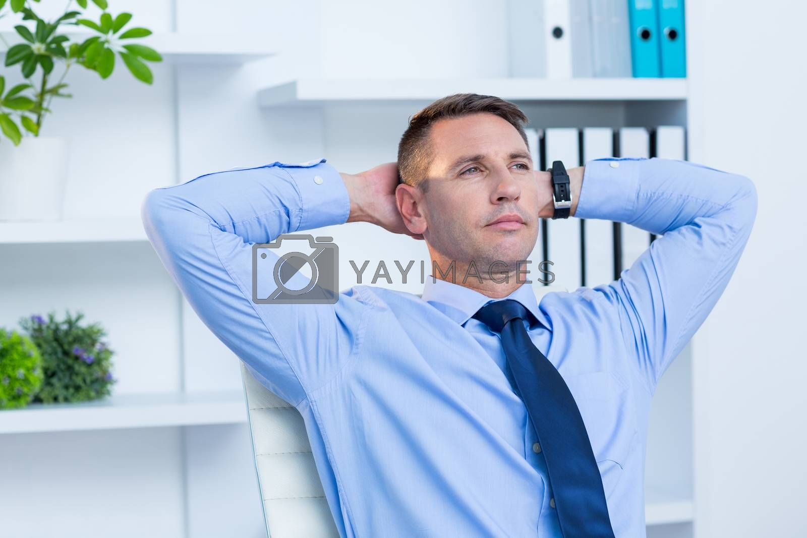 Royalty free image of Serious businessman with hands behind head  by Wavebreakmedia