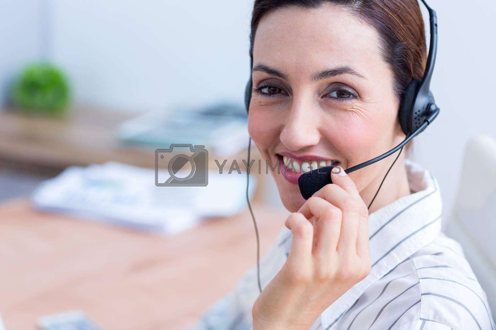 Royalty free image of Portrait brunette businesswoman using headphone  by Wavebreakmedia