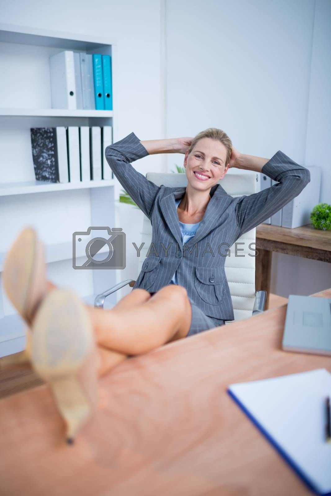 Royalty free image of Smiling blonde businesswoman relaxing herself by Wavebreakmedia