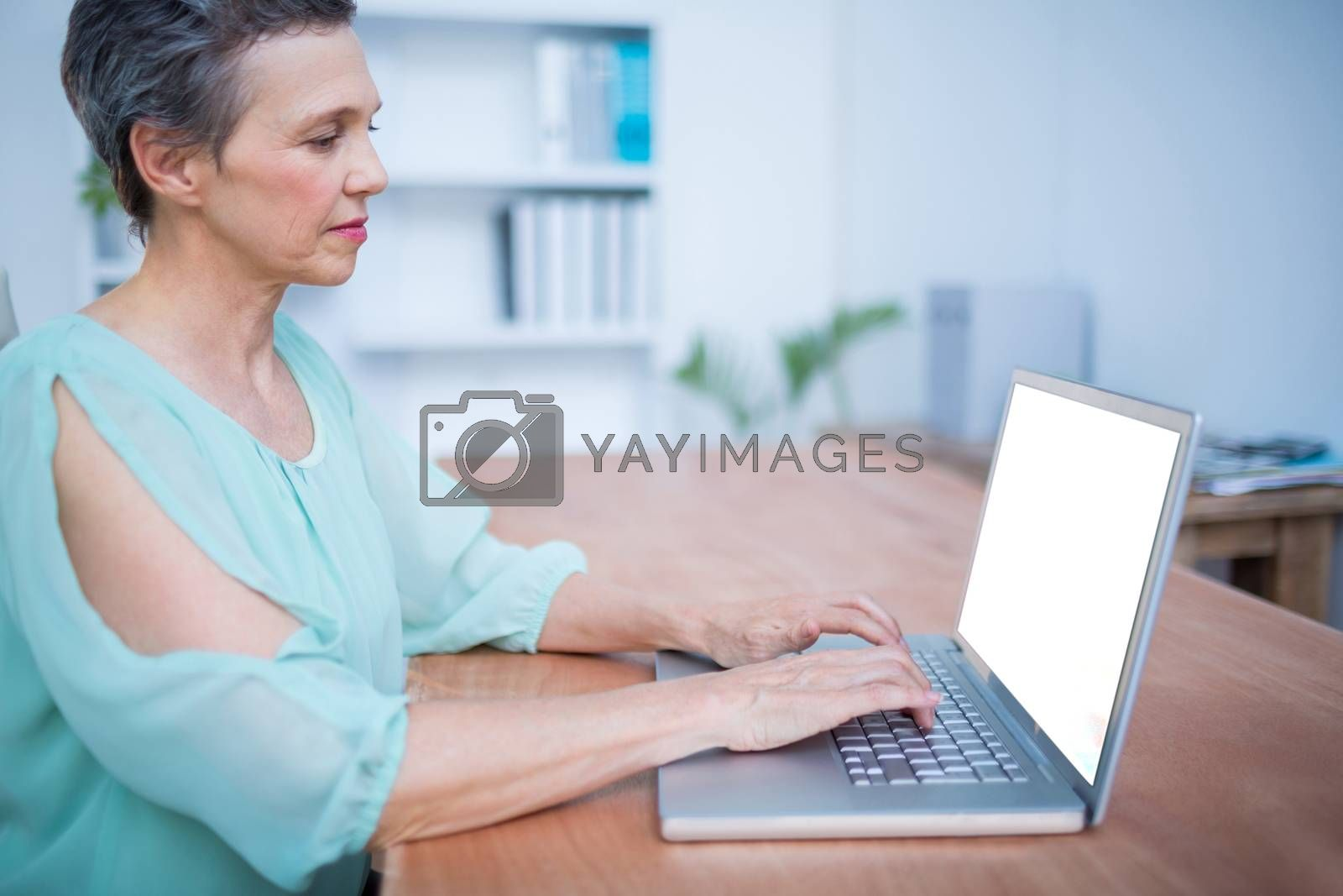 Royalty free image of Attentive businesswoman working on laptop by Wavebreakmedia