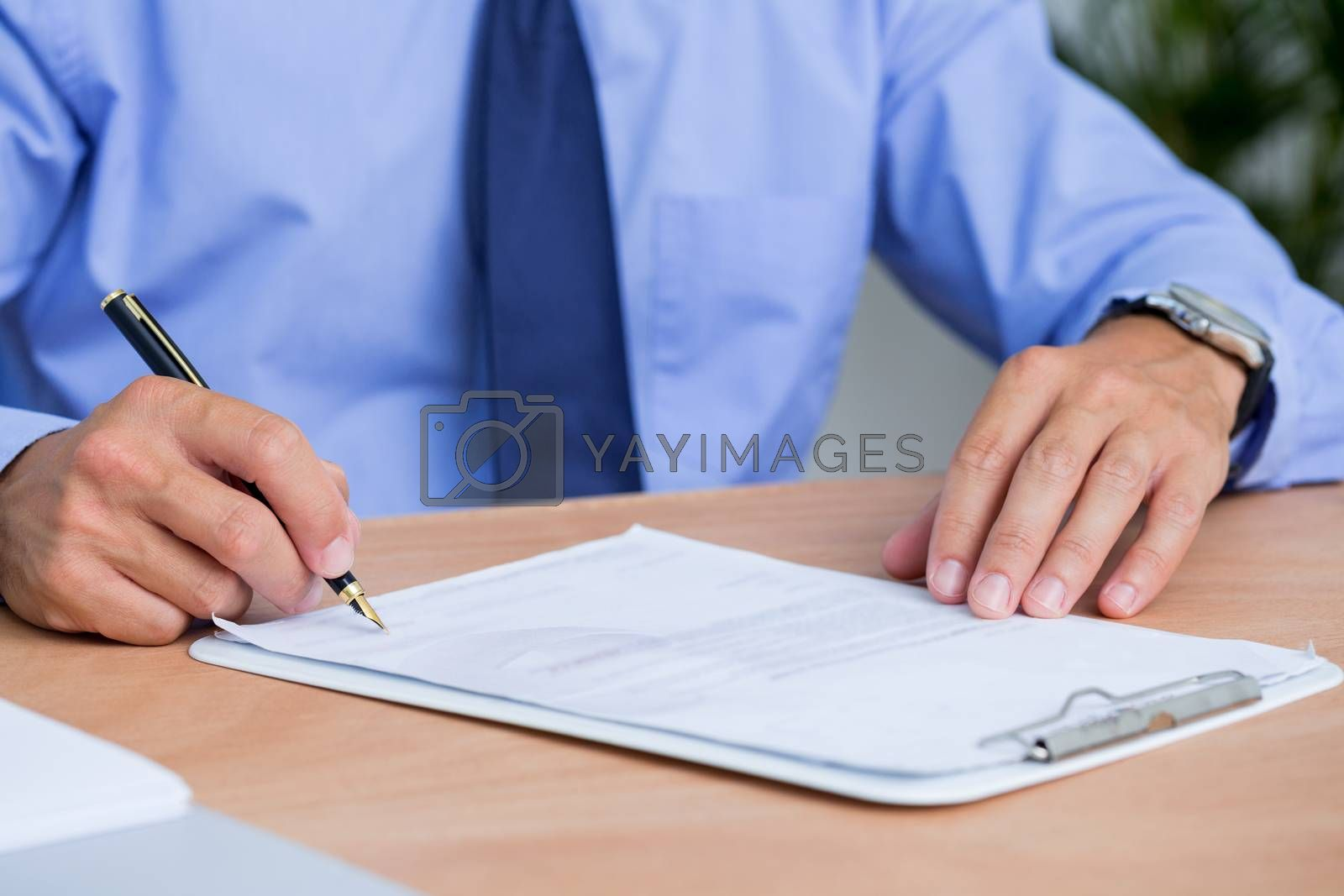 Royalty free image of Businessman signing a contract in the office by Wavebreakmedia