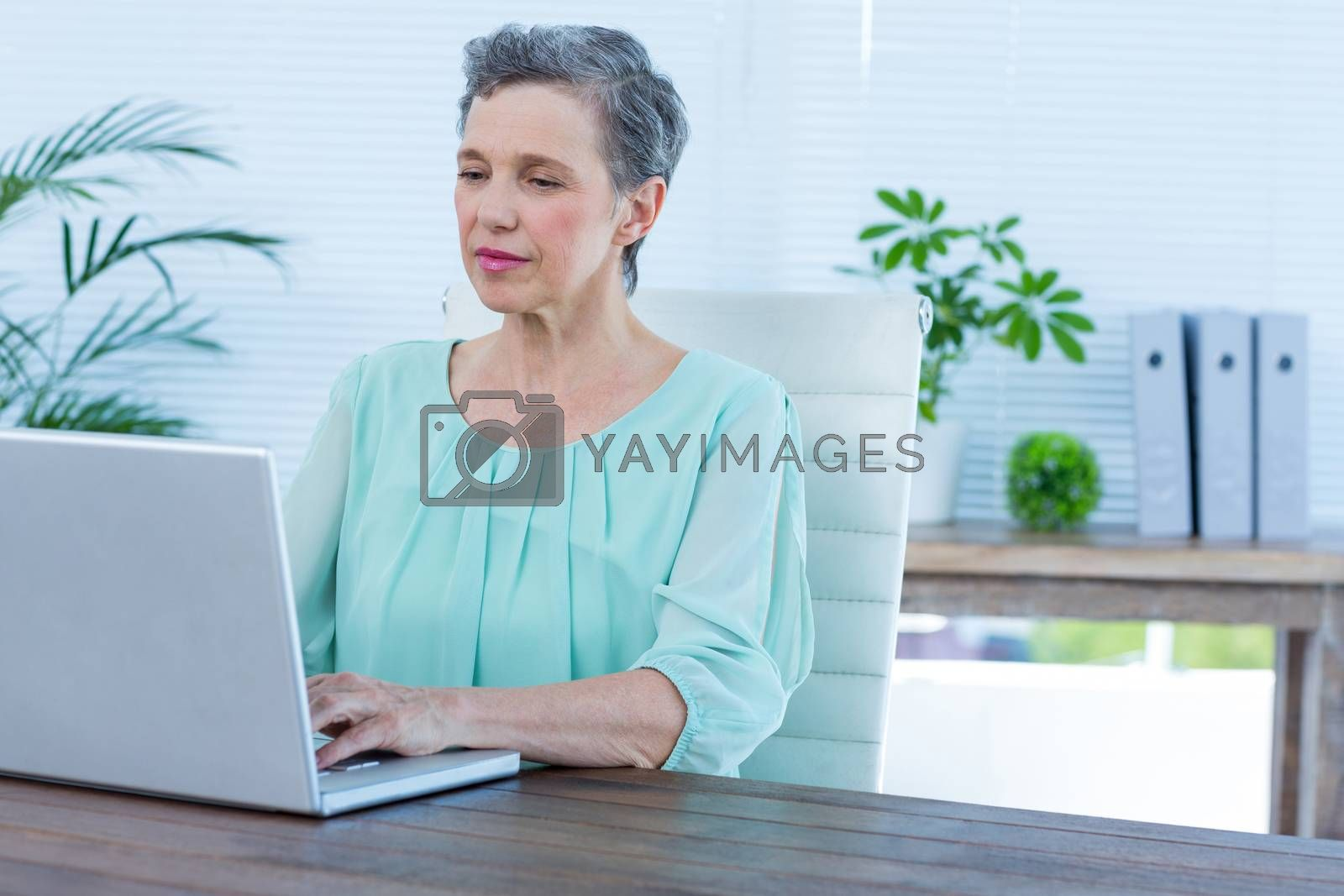 Royalty free image of Attentive businesswoman working on her laptop by Wavebreakmedia