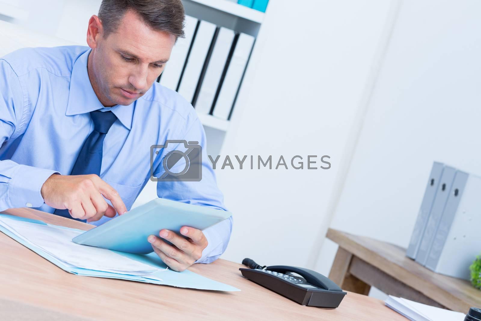 Royalty free image of Serious businessman using digital tablet  by Wavebreakmedia
