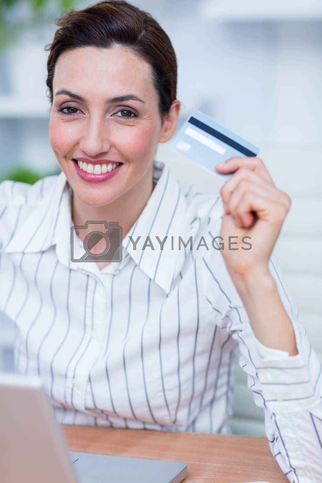 Royalty free image of Pretty brunette businesswoman using her credit card  by Wavebreakmedia