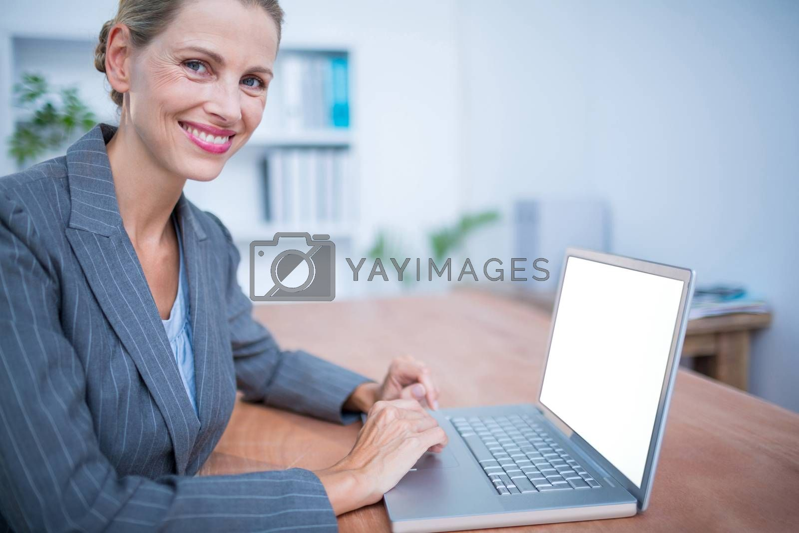 Royalty free image of Smiling blonde businesswoman working on laptop by Wavebreakmedia