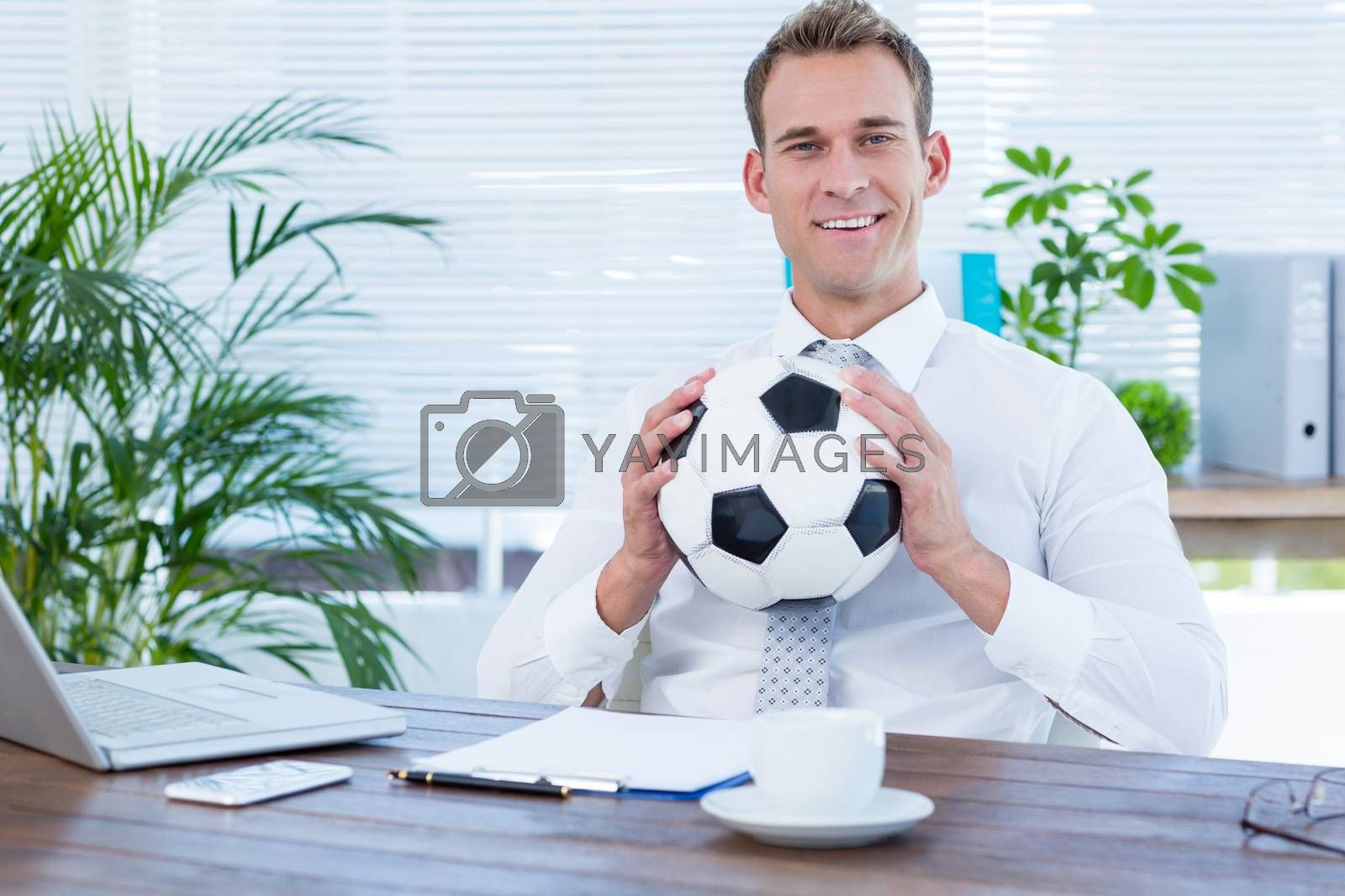Royalty free image of Smiling businessman holding a football by Wavebreakmedia