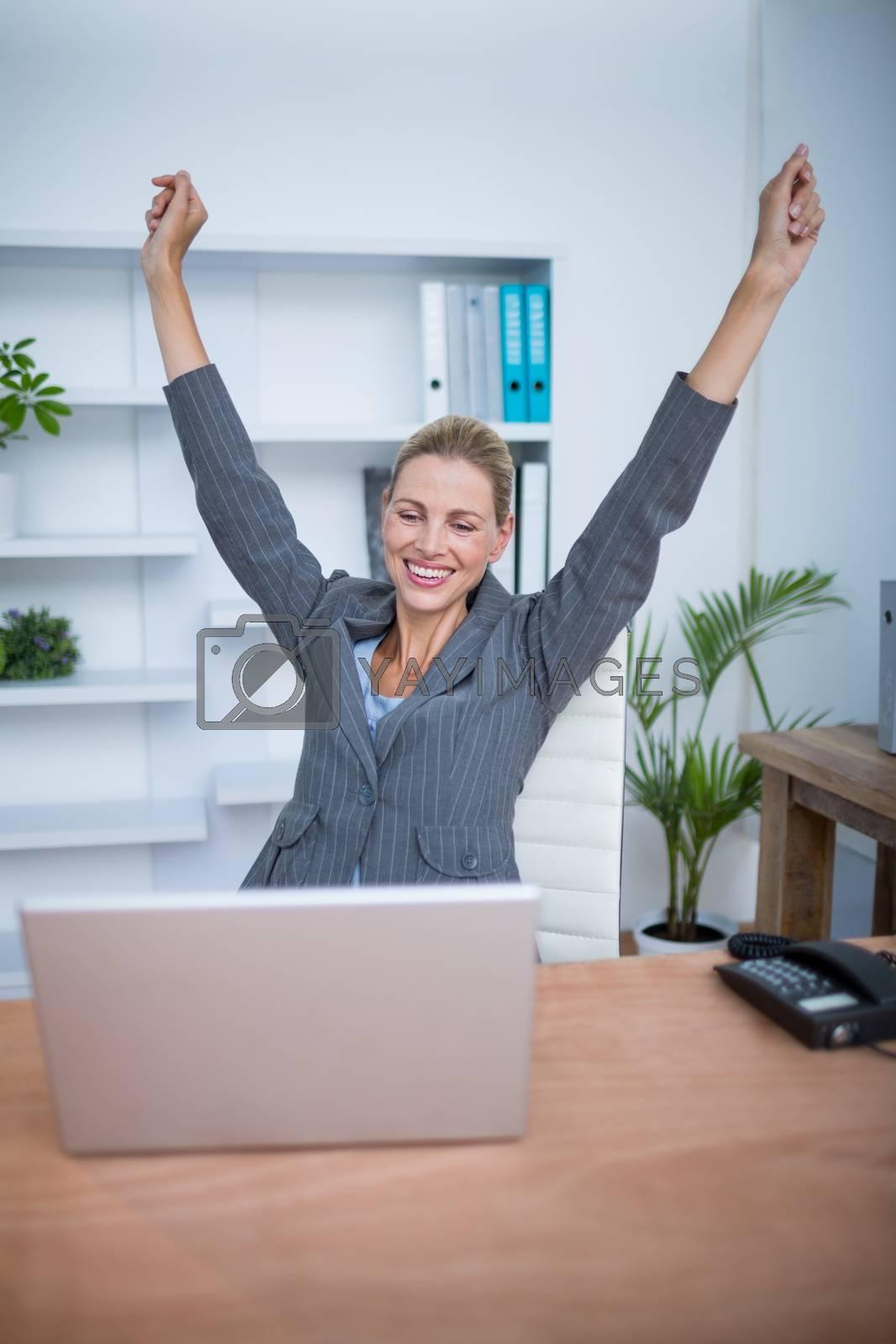 Royalty free image of Pretty blonde businesswoman gesturing victory by Wavebreakmedia