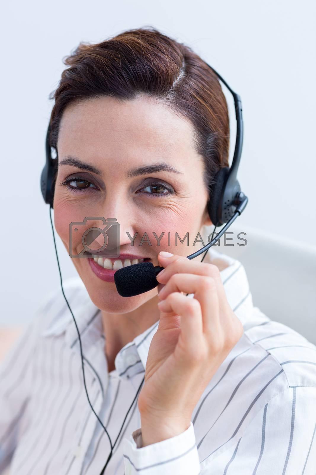 Royalty free image of Portrait brunette businesswoman smiling using headphone by Wavebreakmedia
