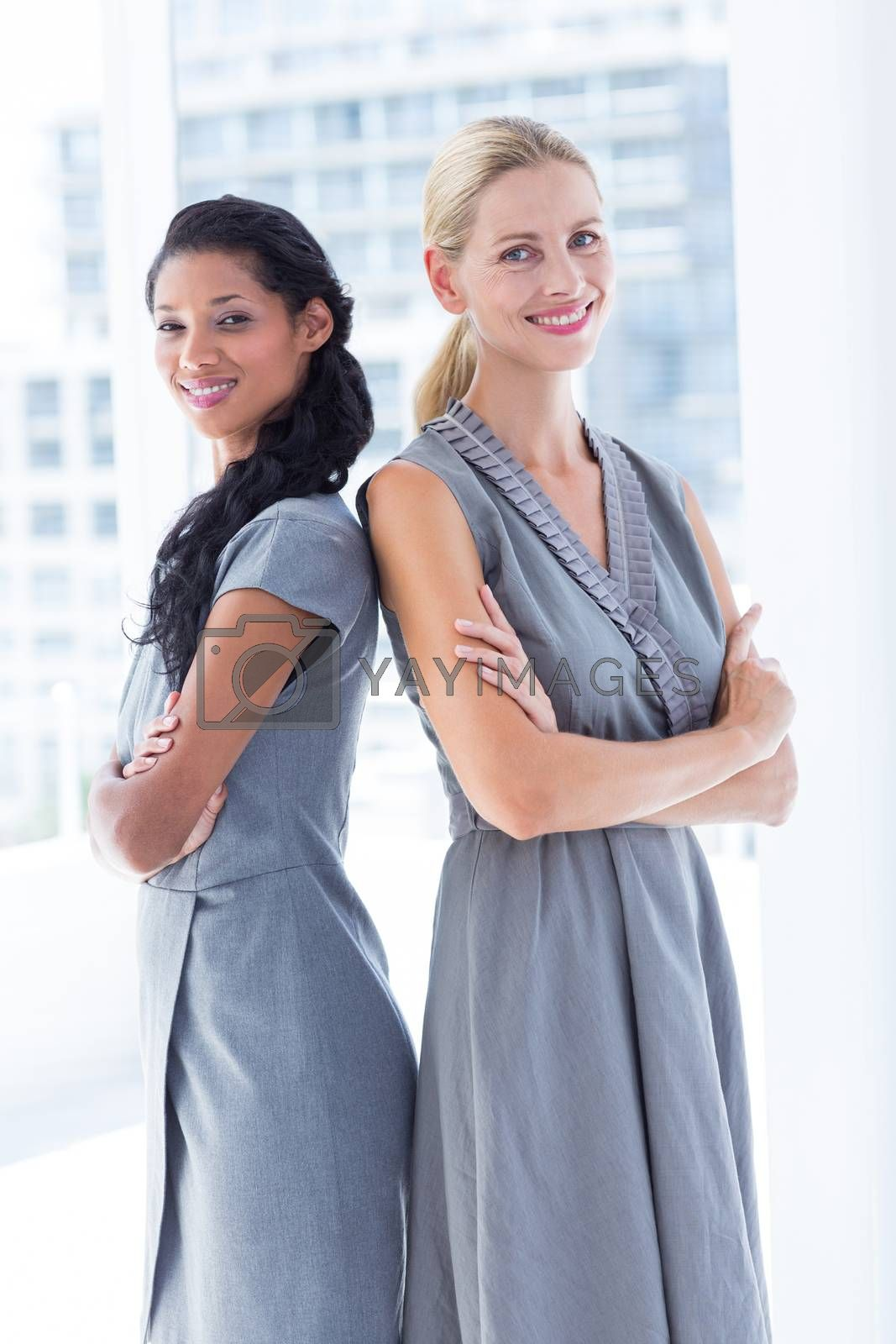 Royalty free image of Back to back businesswomen looking at the camera by Wavebreakmedia