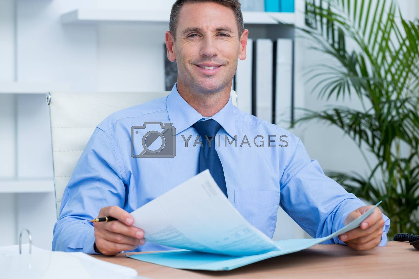Royalty free image of Smiling businessman reading a contrat before signing it by Wavebreakmedia