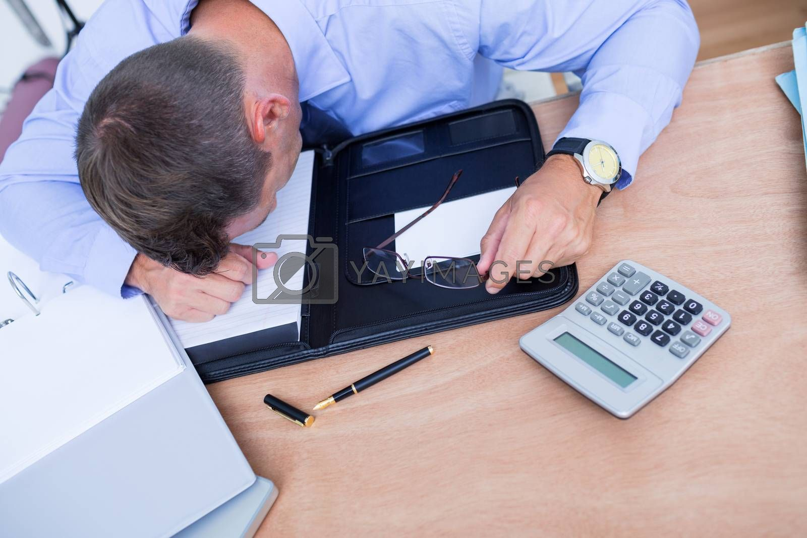 Royalty free image of Exhausted businessman sleeping on the desk by Wavebreakmedia