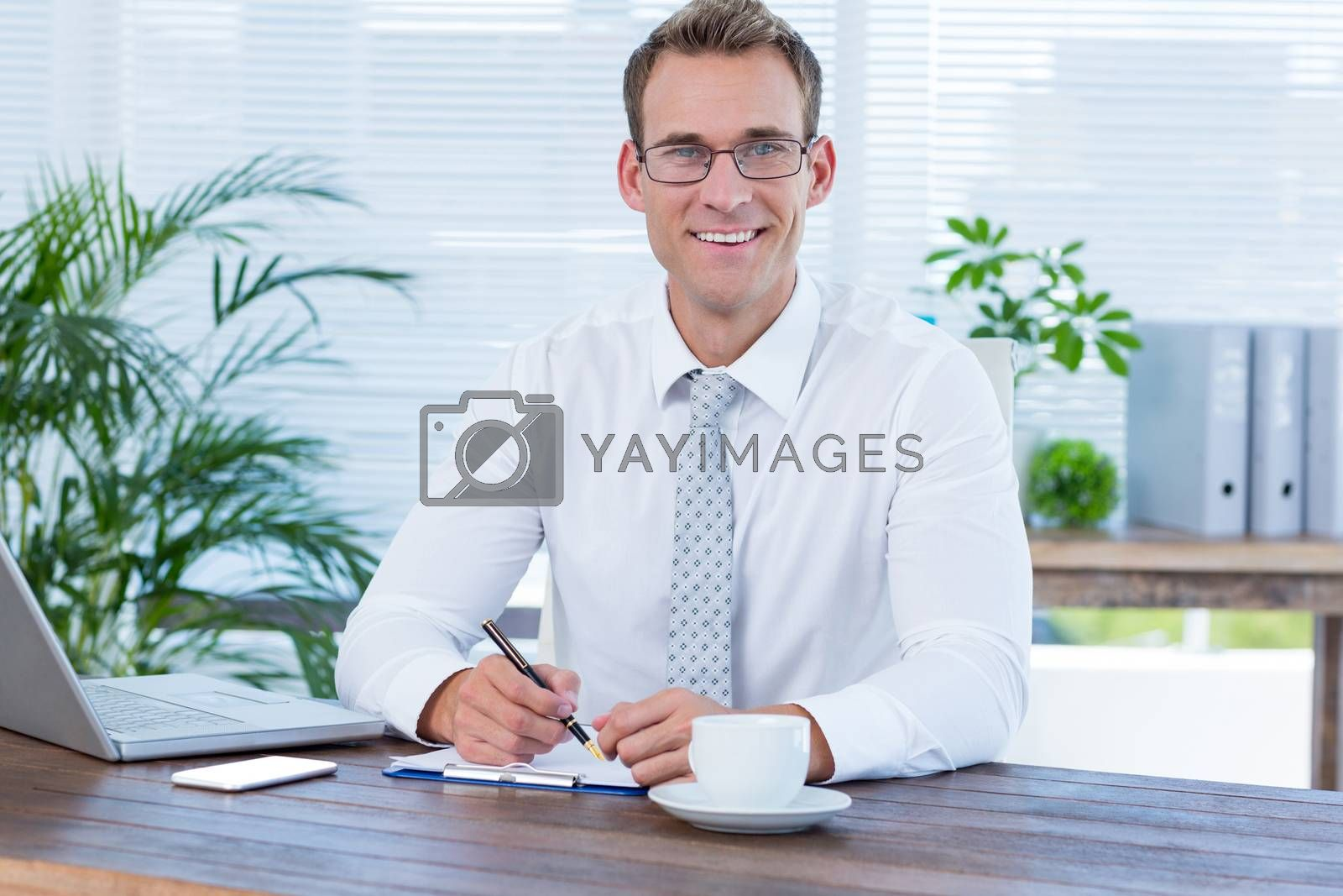 Royalty free image of Smiling businessman writing on notebook by Wavebreakmedia