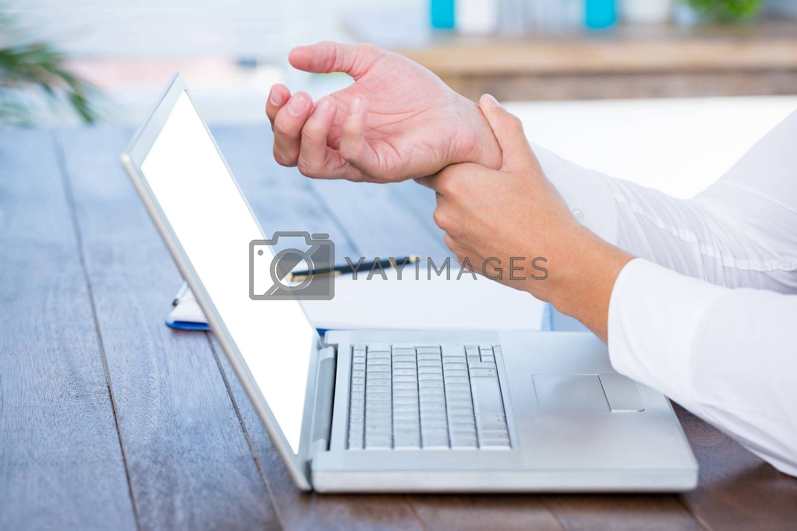 Royalty free image of Close up view of man massaging his wrist by Wavebreakmedia