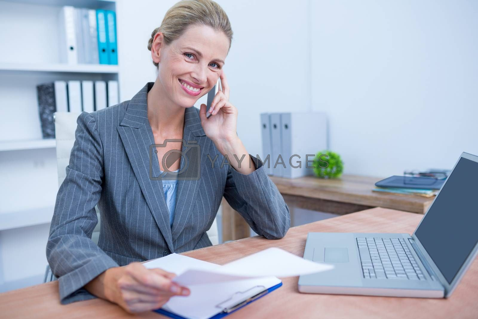 Royalty free image of Pretty blonde businesswoman phoning and using her laptop by Wavebreakmedia
