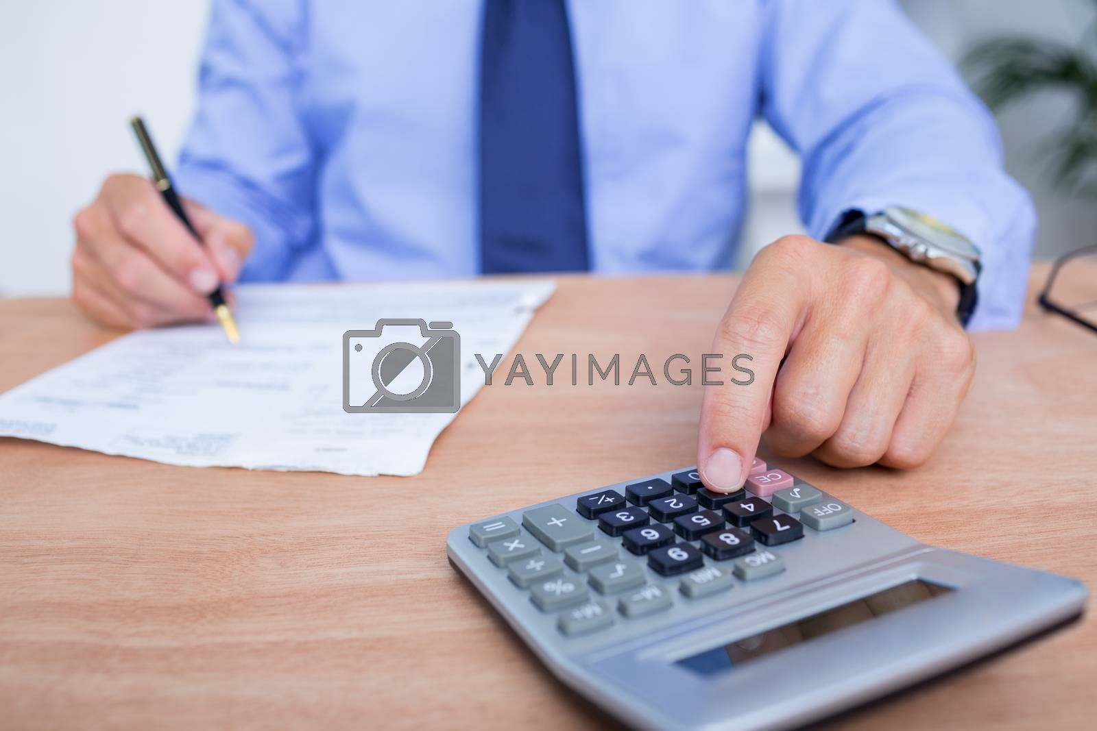 Royalty free image of Businessman using the calculator while writing by Wavebreakmedia