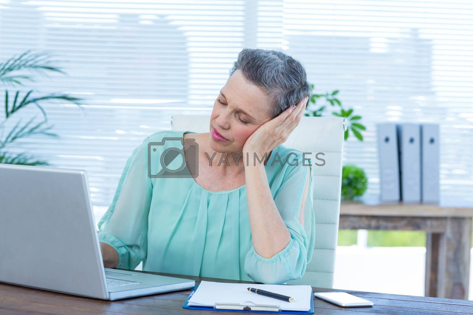 Royalty free image of Tired businesswoman working on laptop by Wavebreakmedia