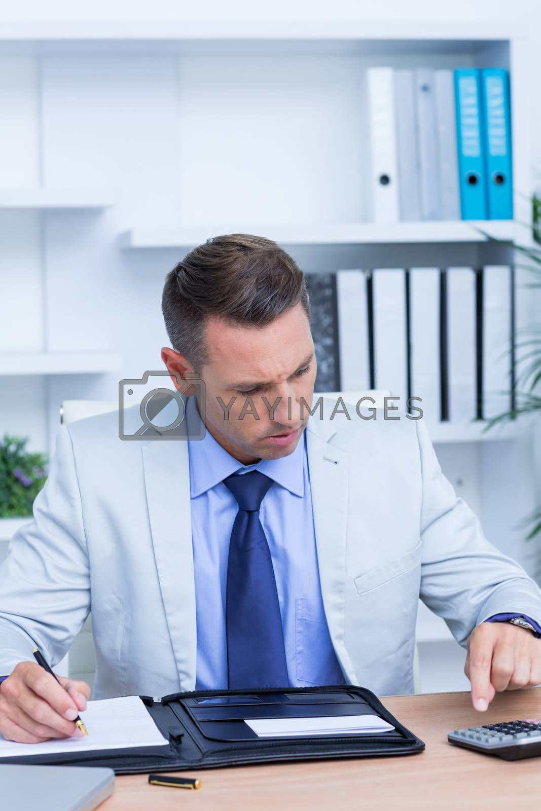 Royalty free image of Professional businessman doing some calculations by Wavebreakmedia