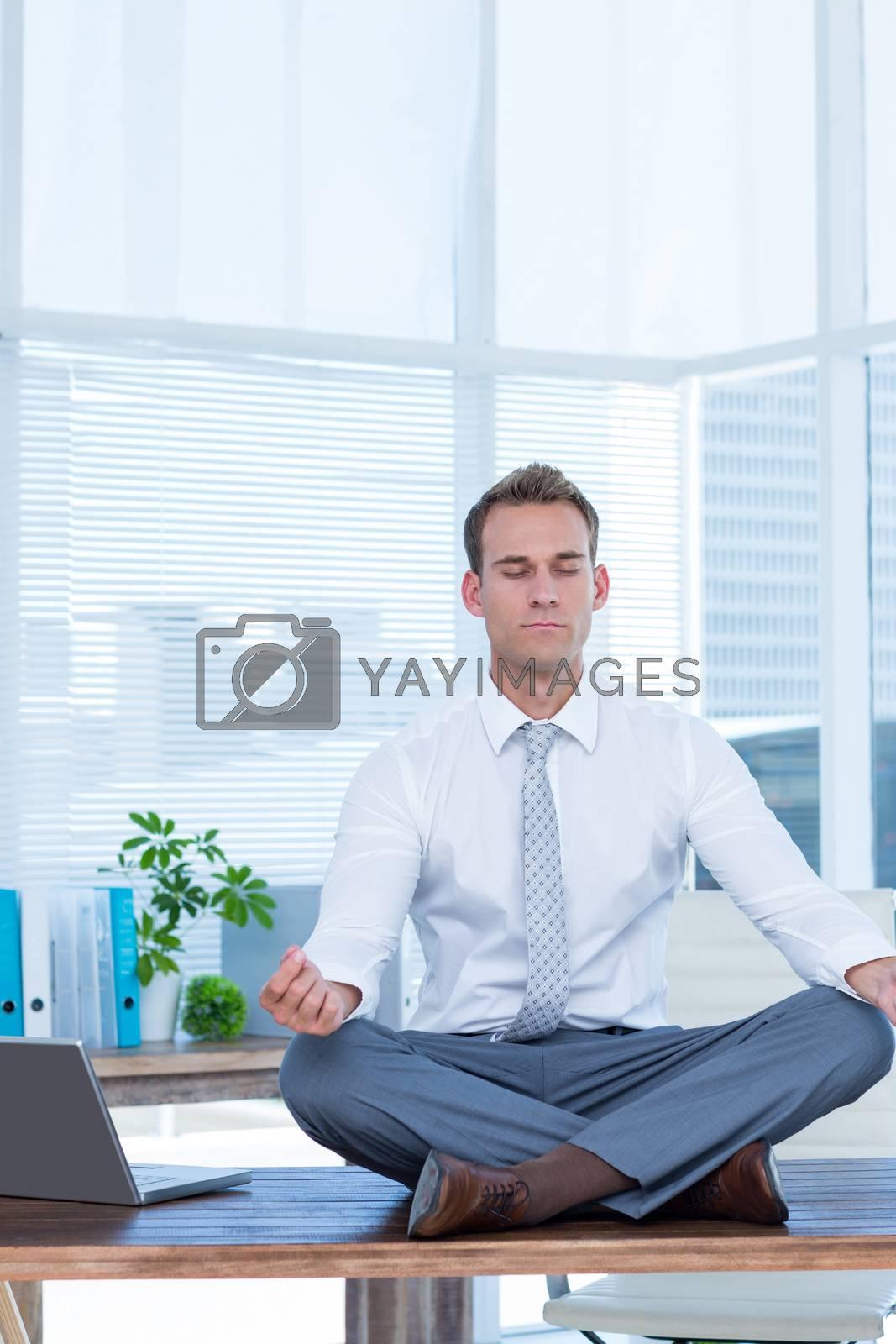 Royalty free image of Zen businessman doing yoga meditation  by Wavebreakmedia