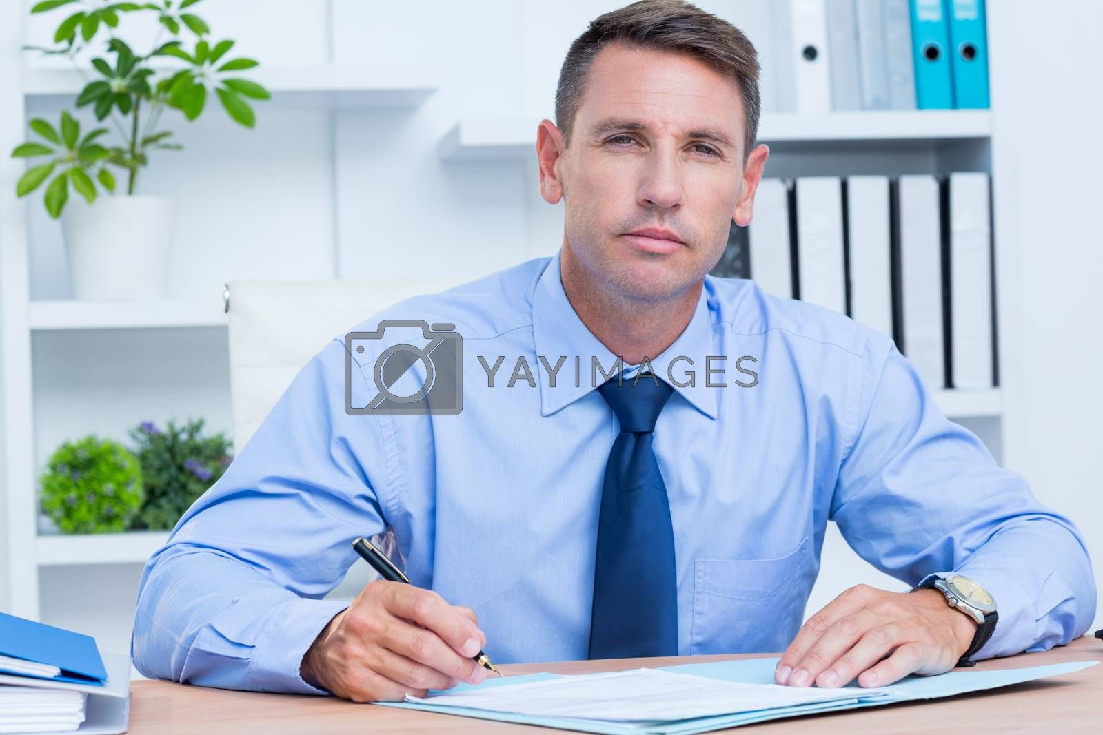Royalty free image of Portrait of serious businessman writing  by Wavebreakmedia