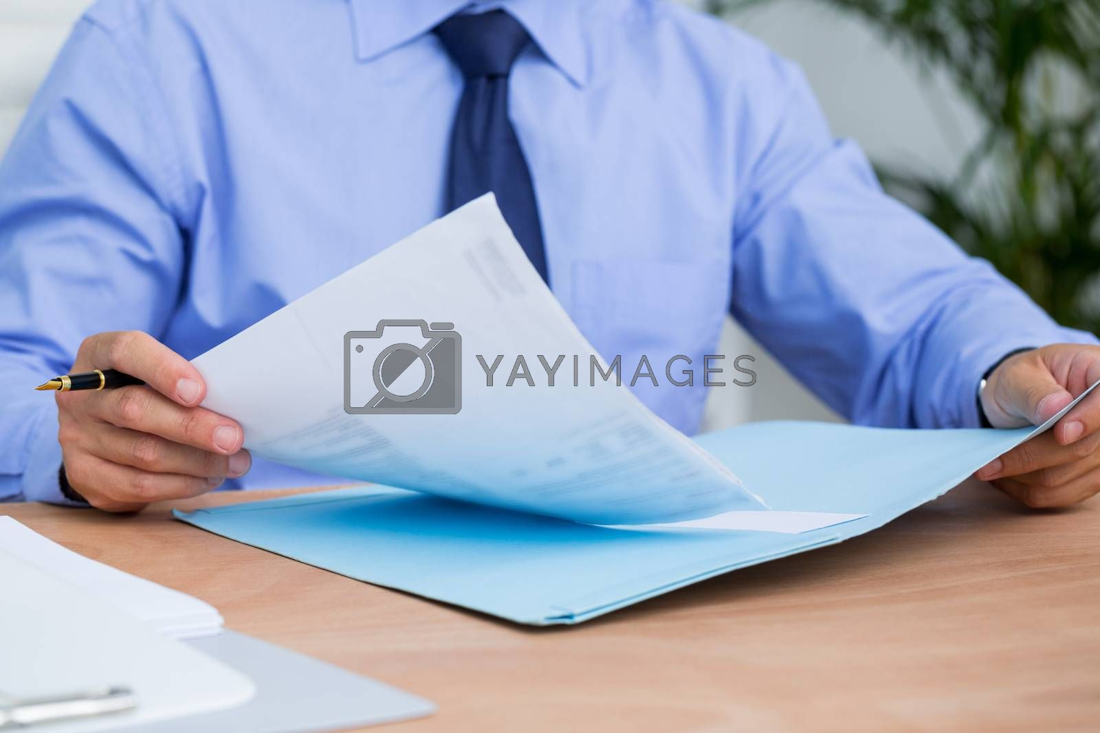 Royalty free image of Businessman reading a contract before signing it by Wavebreakmedia