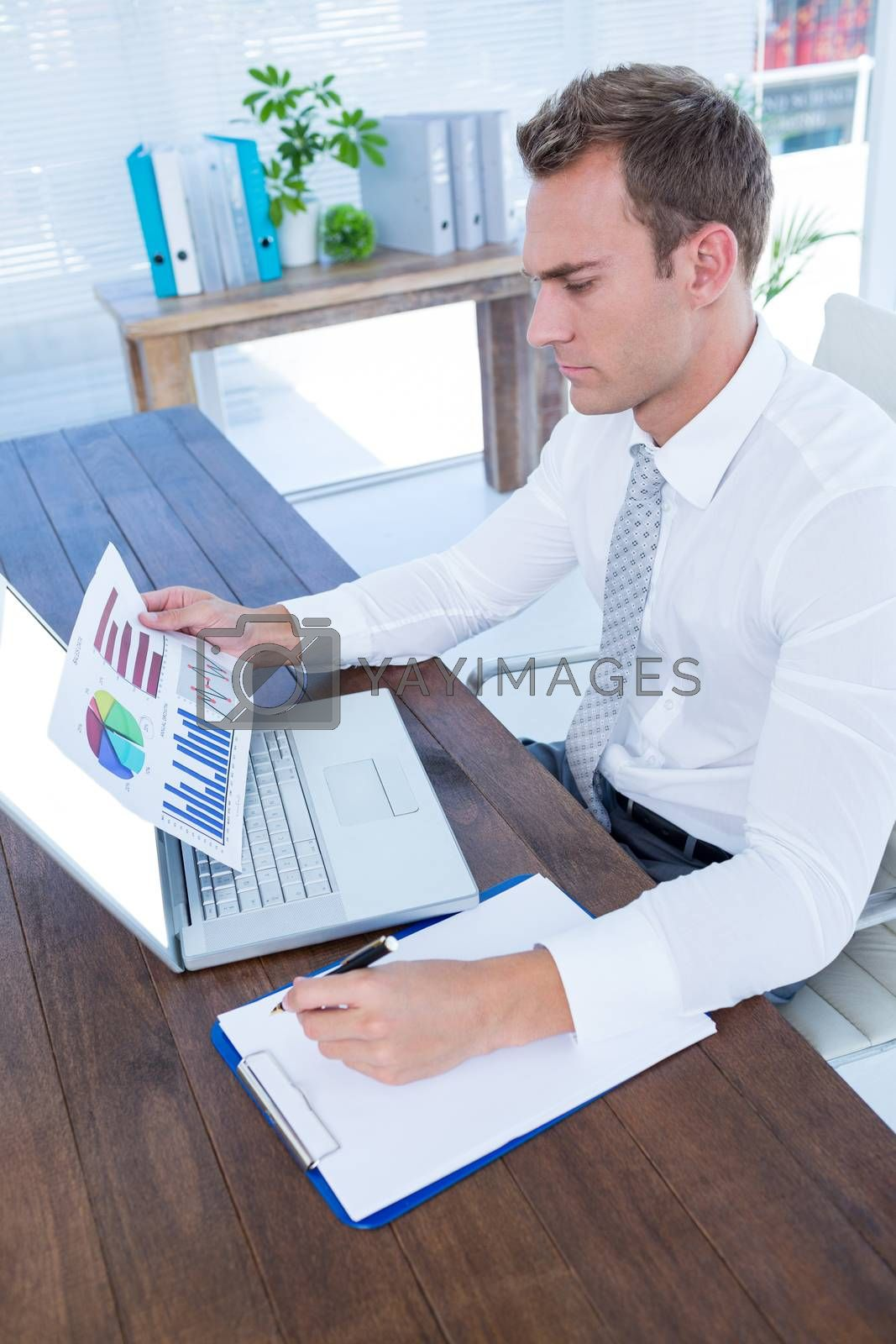 Royalty free image of Attentive businessman working with flow charts by Wavebreakmedia