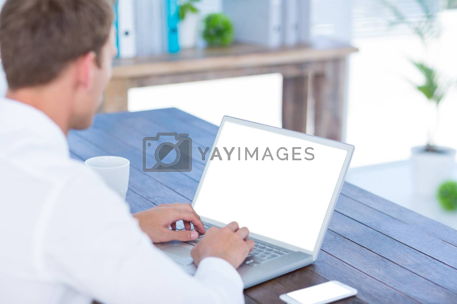 Royalty free image of Back view of a businessman typing on laptop by Wavebreakmedia