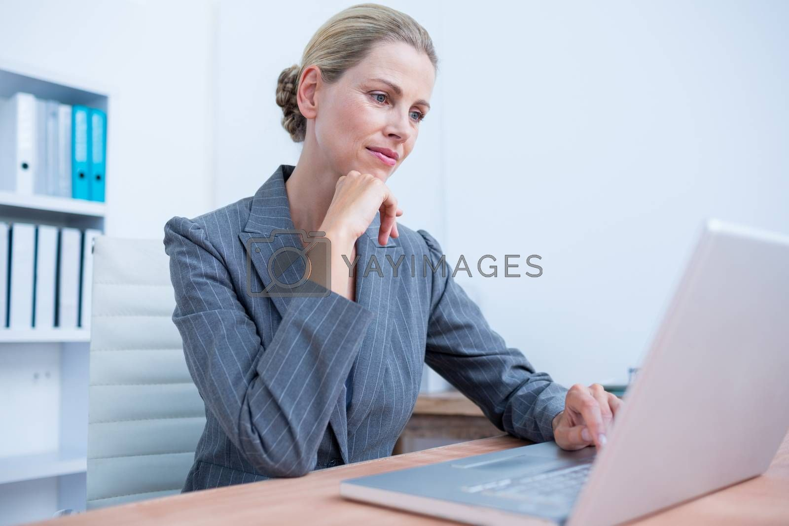 Royalty free image of Pretty blonde businesswoman using her laptop  by Wavebreakmedia
