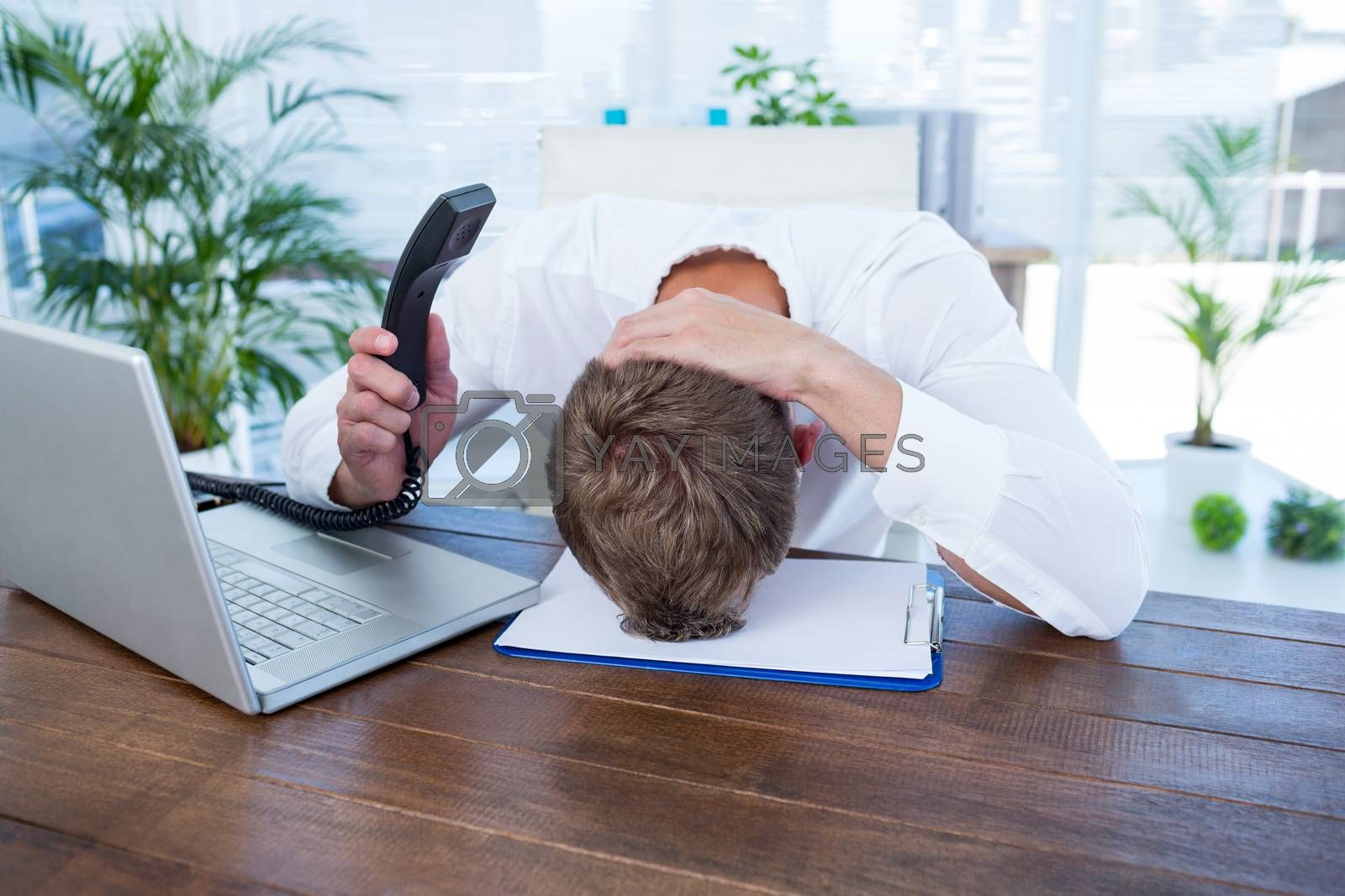 Royalty free image of Irritated businessman holding a land line phone by Wavebreakmedia