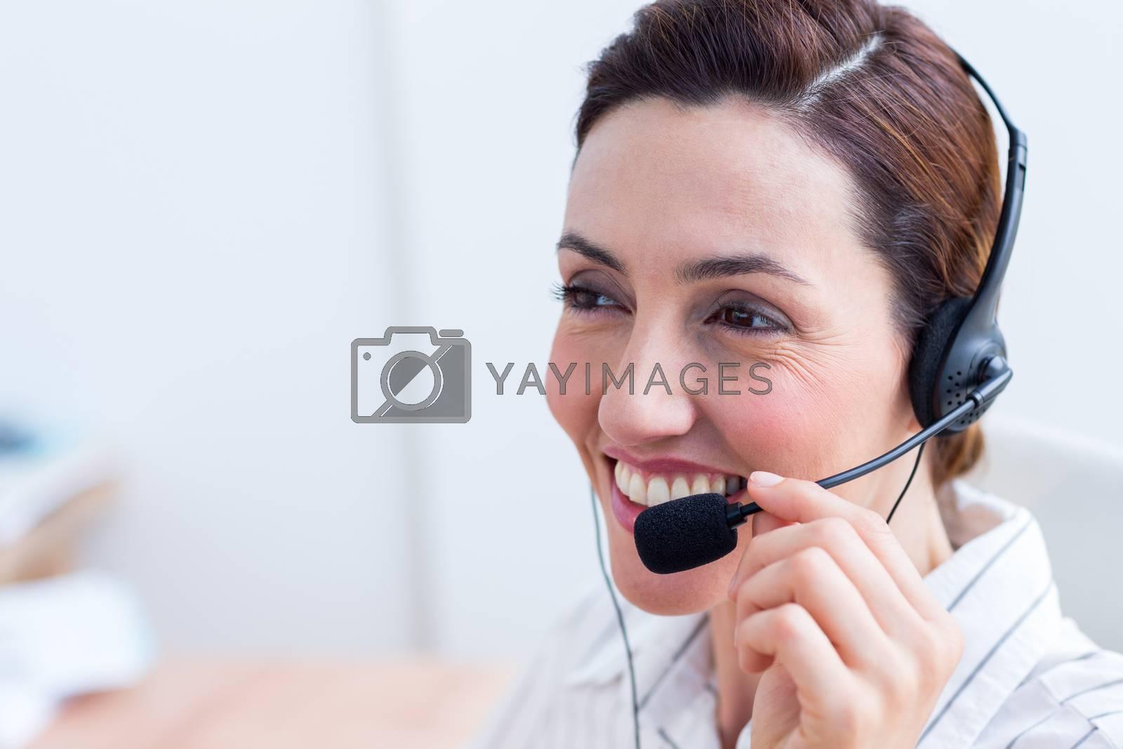 Royalty free image of Brunette smiling using headphone  by Wavebreakmedia