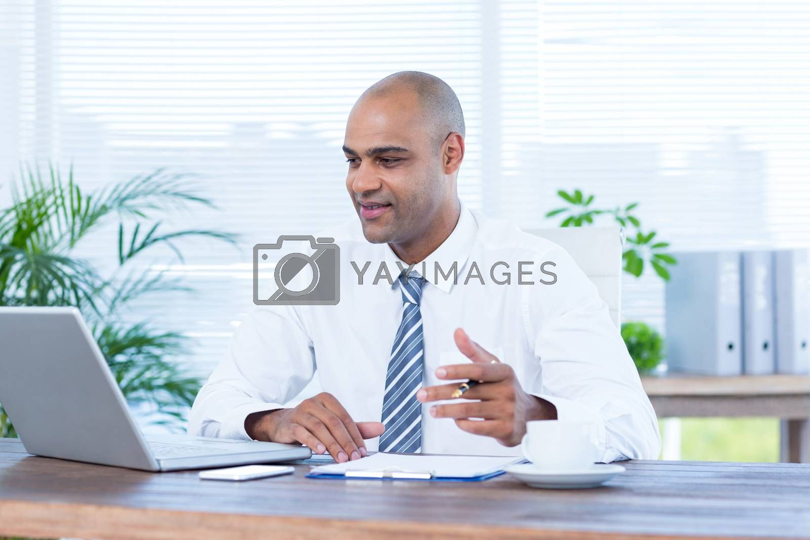 Royalty free image of Smiling businessman working on laptop by Wavebreakmedia