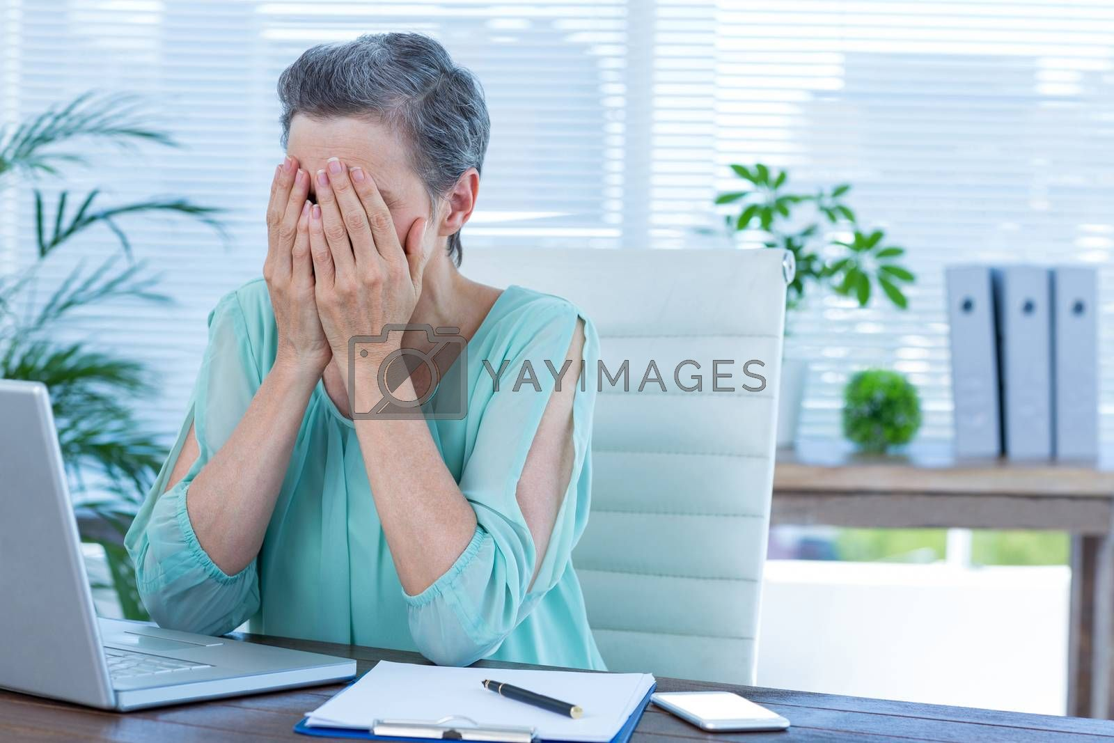 Royalty free image of Anxious businesswoman with head in hands by Wavebreakmedia