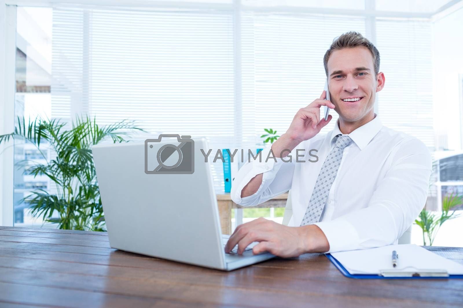 Royalty free image of Smiling businessman talking on the phone by Wavebreakmedia
