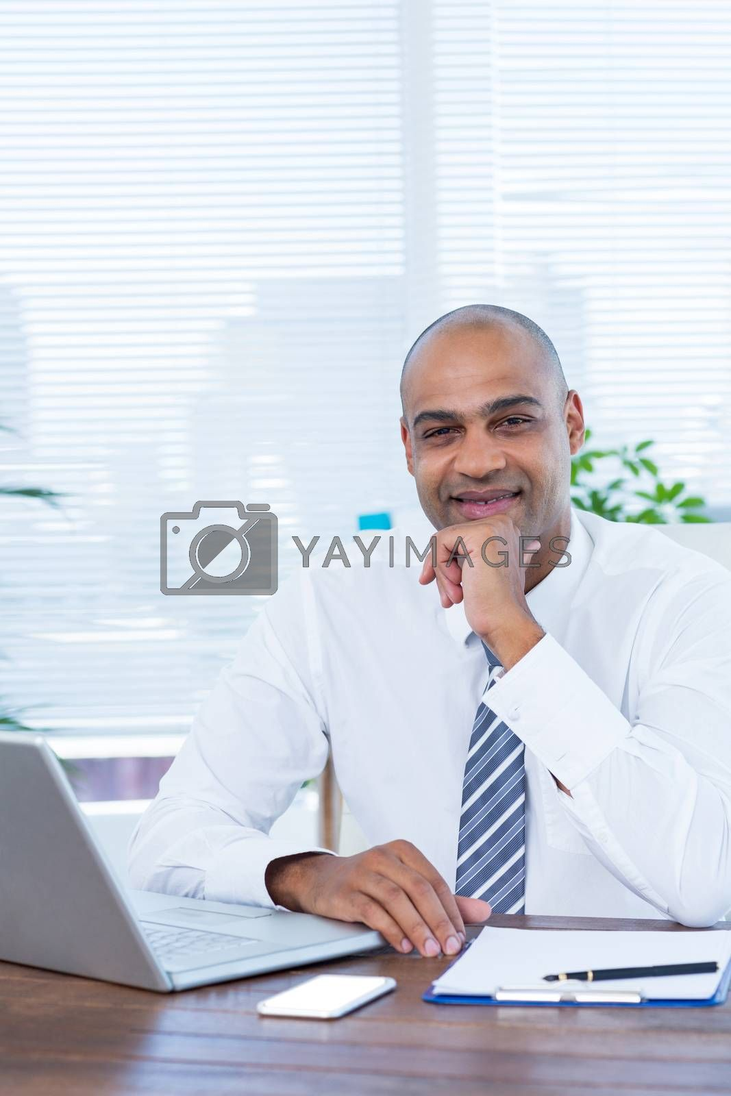 Royalty free image of Smiling businessman looking at the camera by Wavebreakmedia