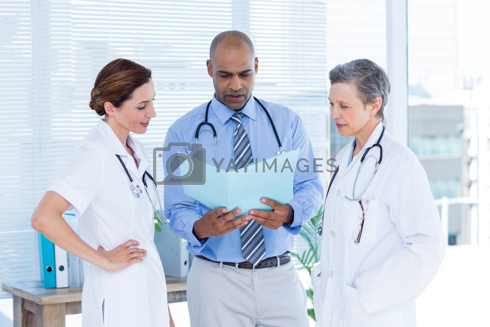 Royalty free image of Concentrated medical colleagues analyzing file together by Wavebreakmedia