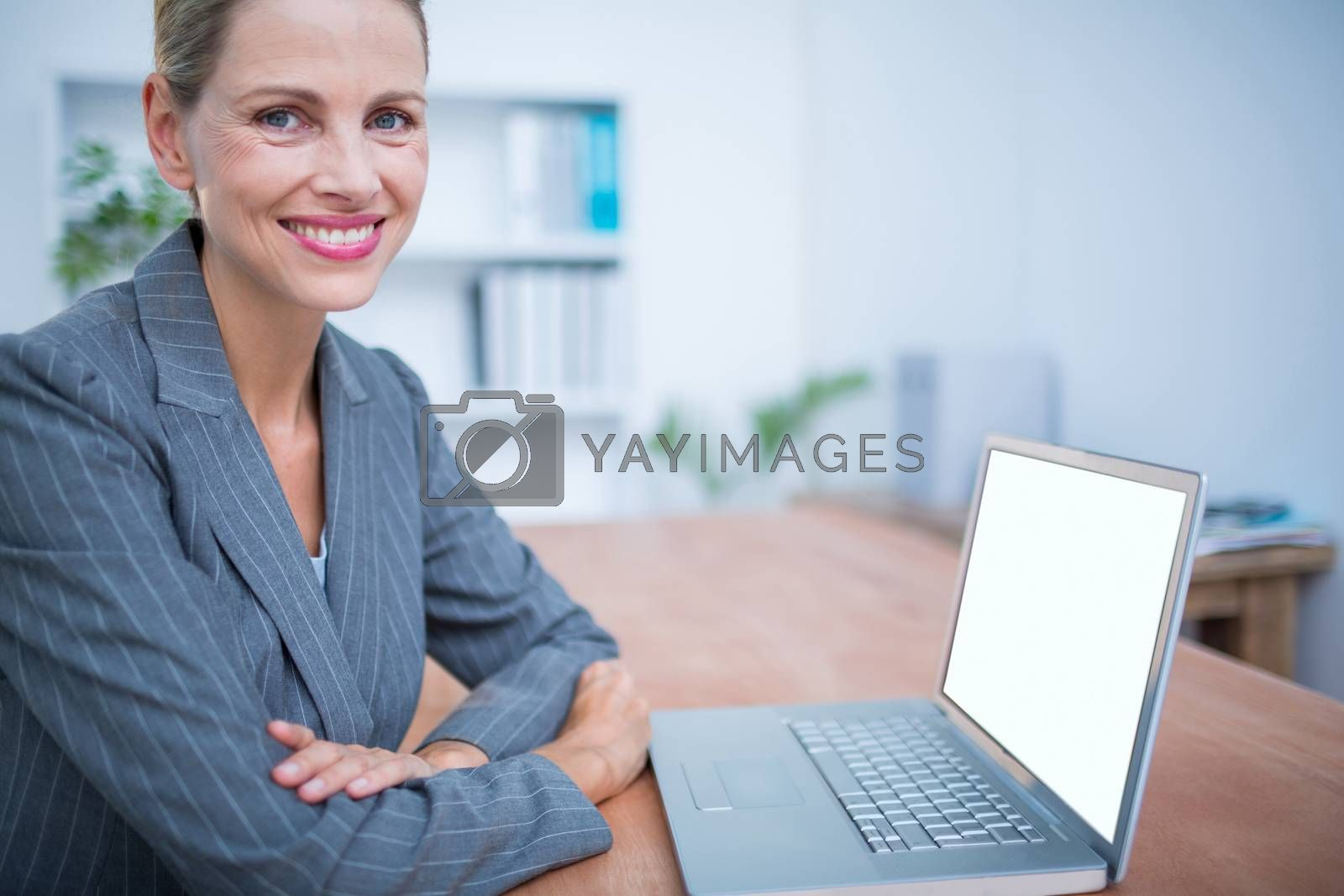 Royalty free image of Smiling businesswoman in front of her laptop by Wavebreakmedia
