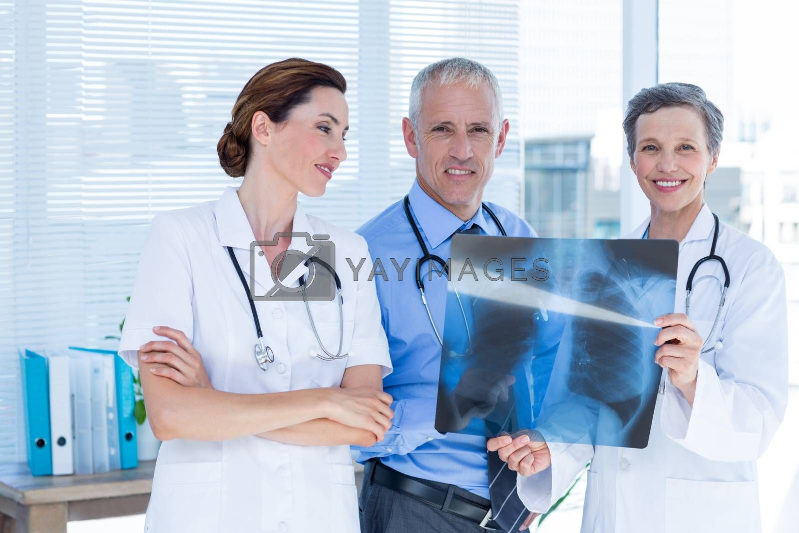 Royalty free image of Portrait of smiling medical colleagues examining x-ray together by Wavebreakmedia