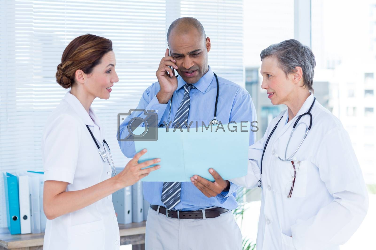 Royalty free image of Concentrated doctor showing file to his colleagues while calling by Wavebreakmedia