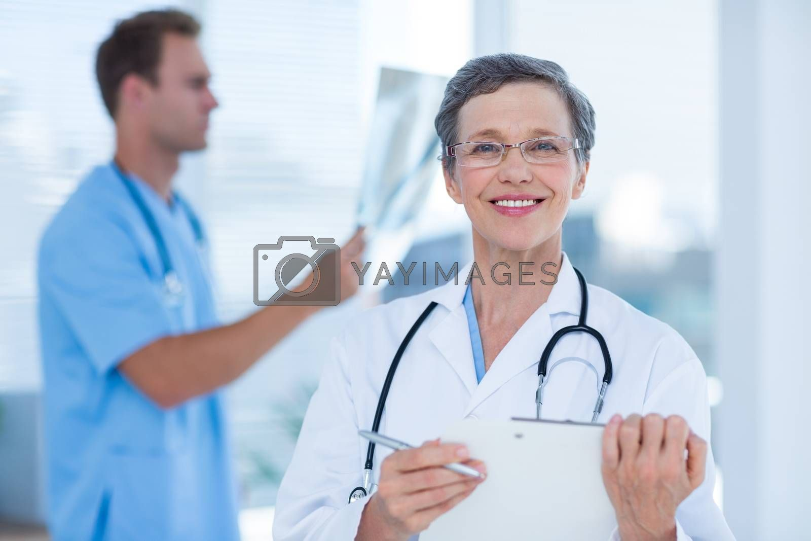 Royalty free image of Smiling doctor holding a clipboard by Wavebreakmedia