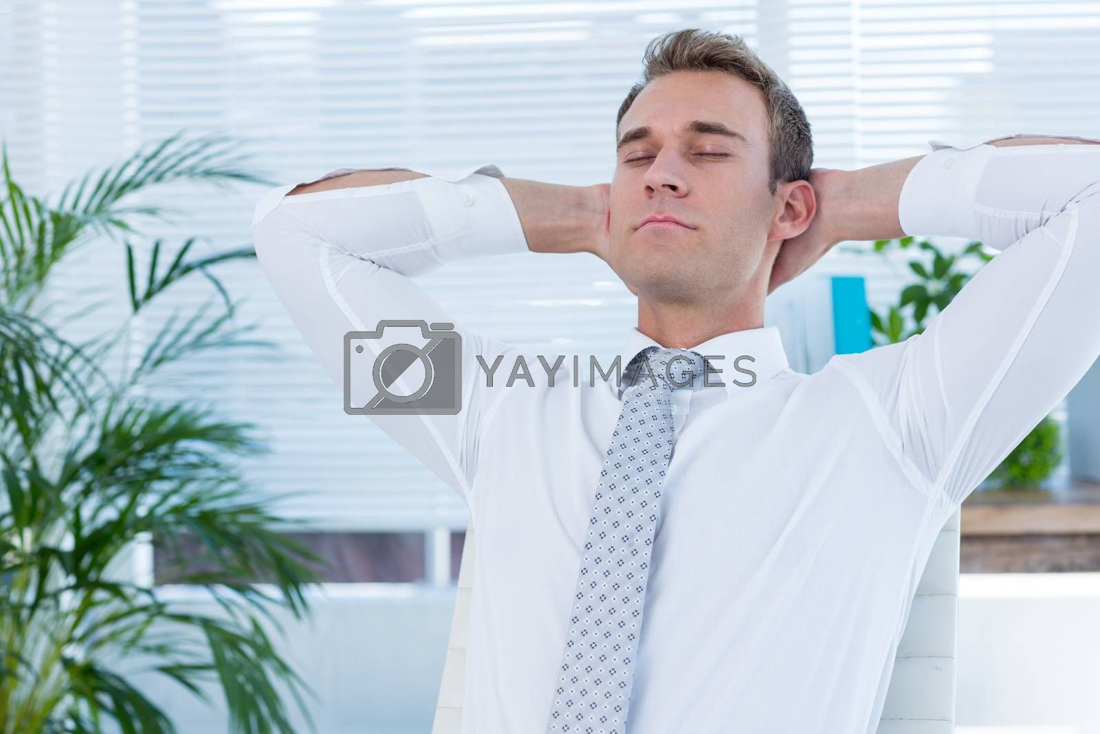 Royalty free image of Relaxed businessman lying down in swivel chair by Wavebreakmedia