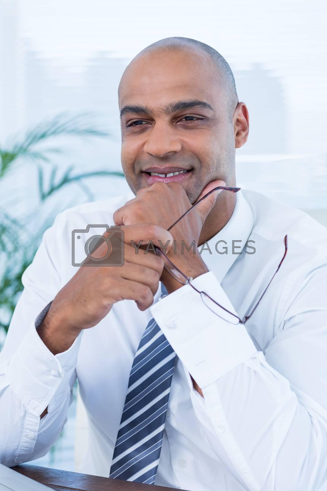 Royalty free image of Smiling businessman holding reading glasses by Wavebreakmedia