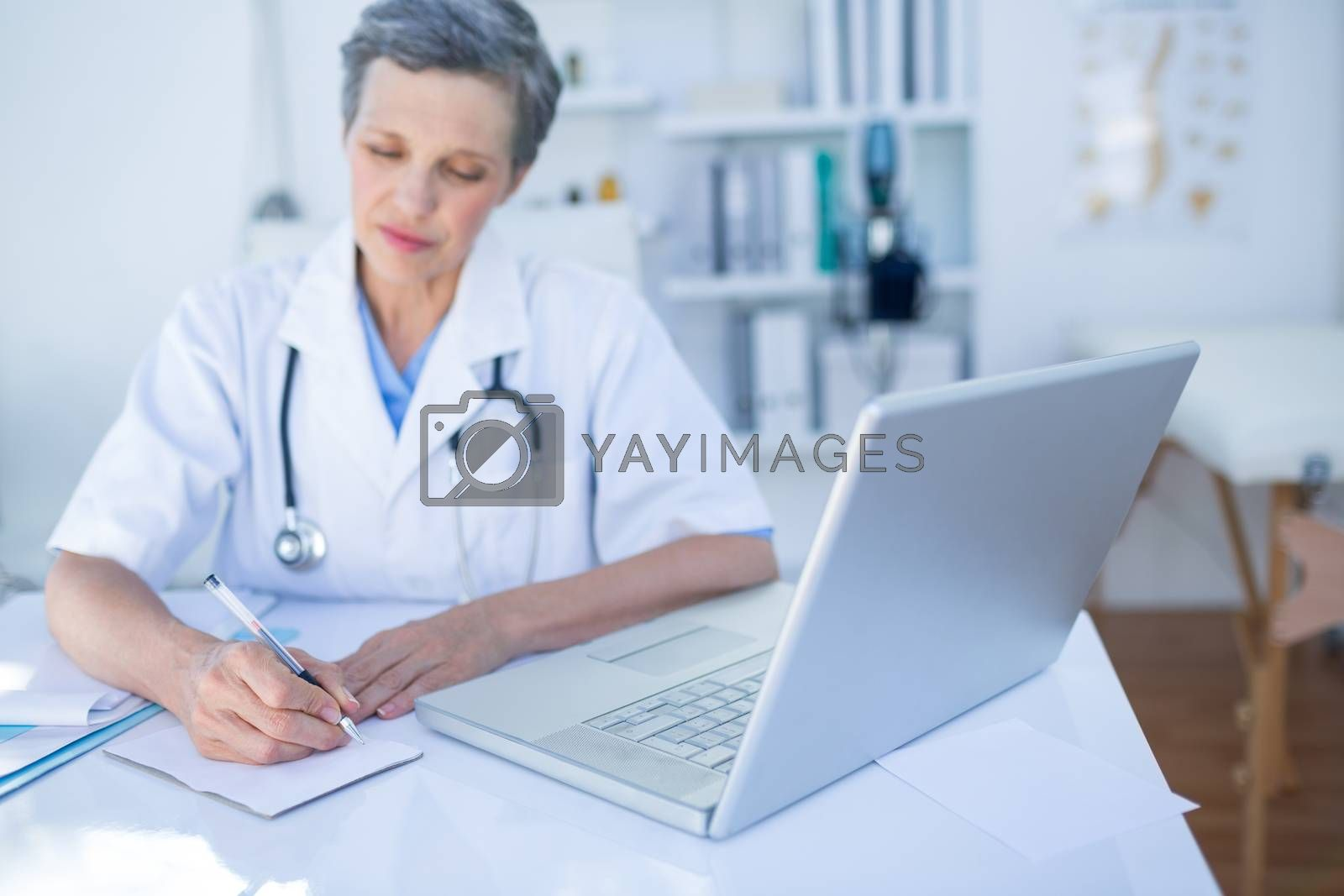 Royalty free image of Female doctor writing on paper  by Wavebreakmedia