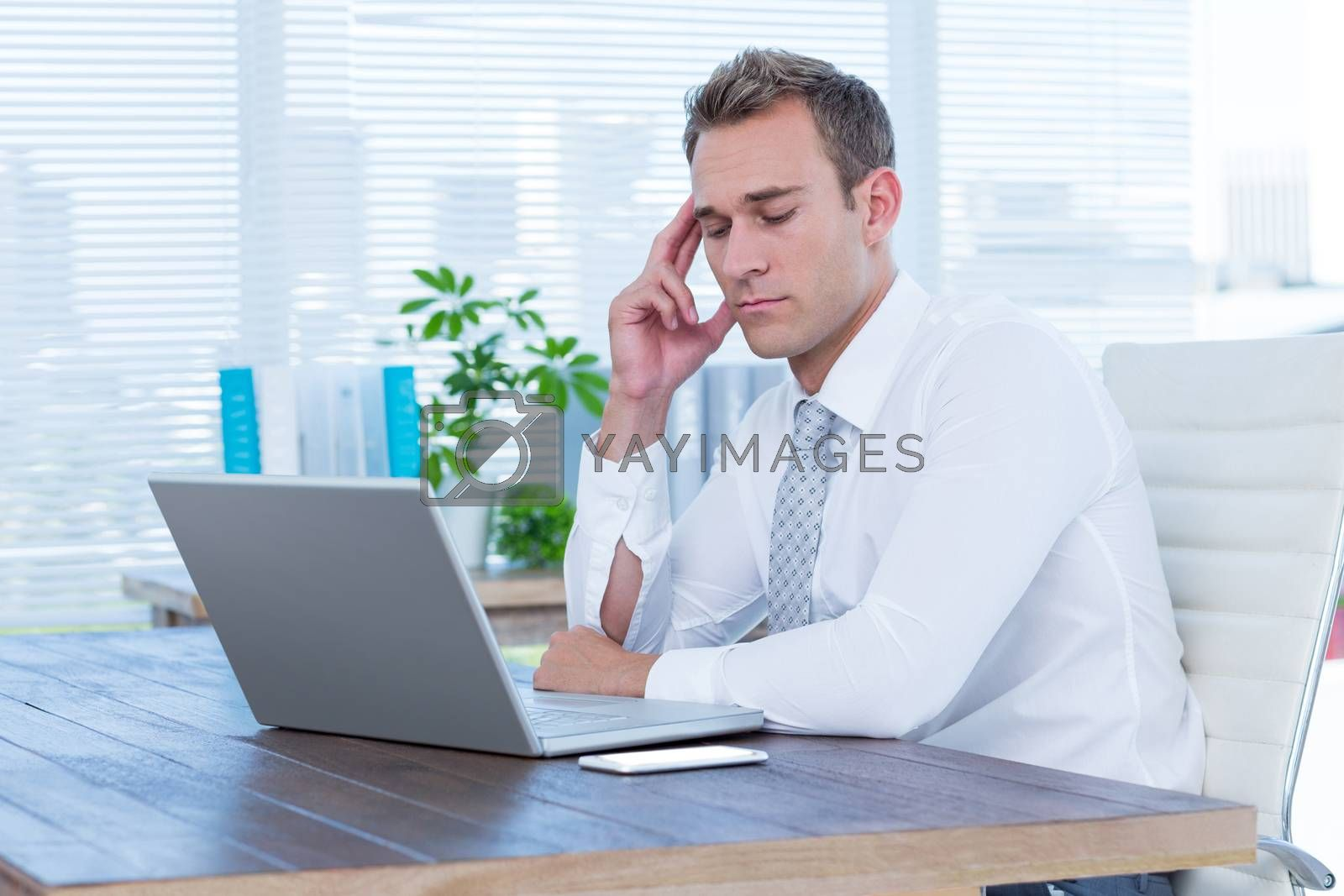 Royalty free image of Exhausted businessman drowsing on his laptop by Wavebreakmedia