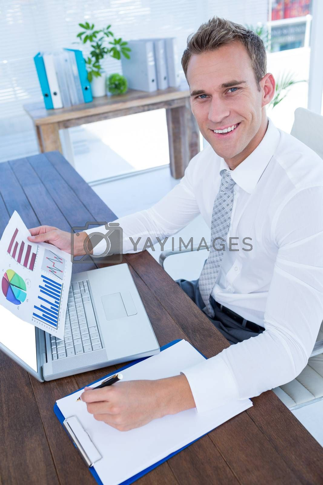 Royalty free image of Smiling businessman working with flow charts by Wavebreakmedia