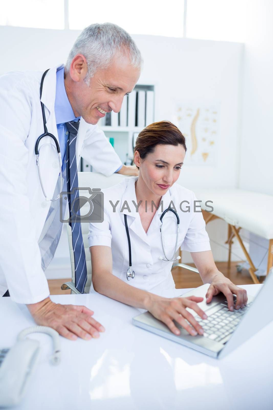 Royalty free image of Smiling medical colleagues working with laptop by Wavebreakmedia