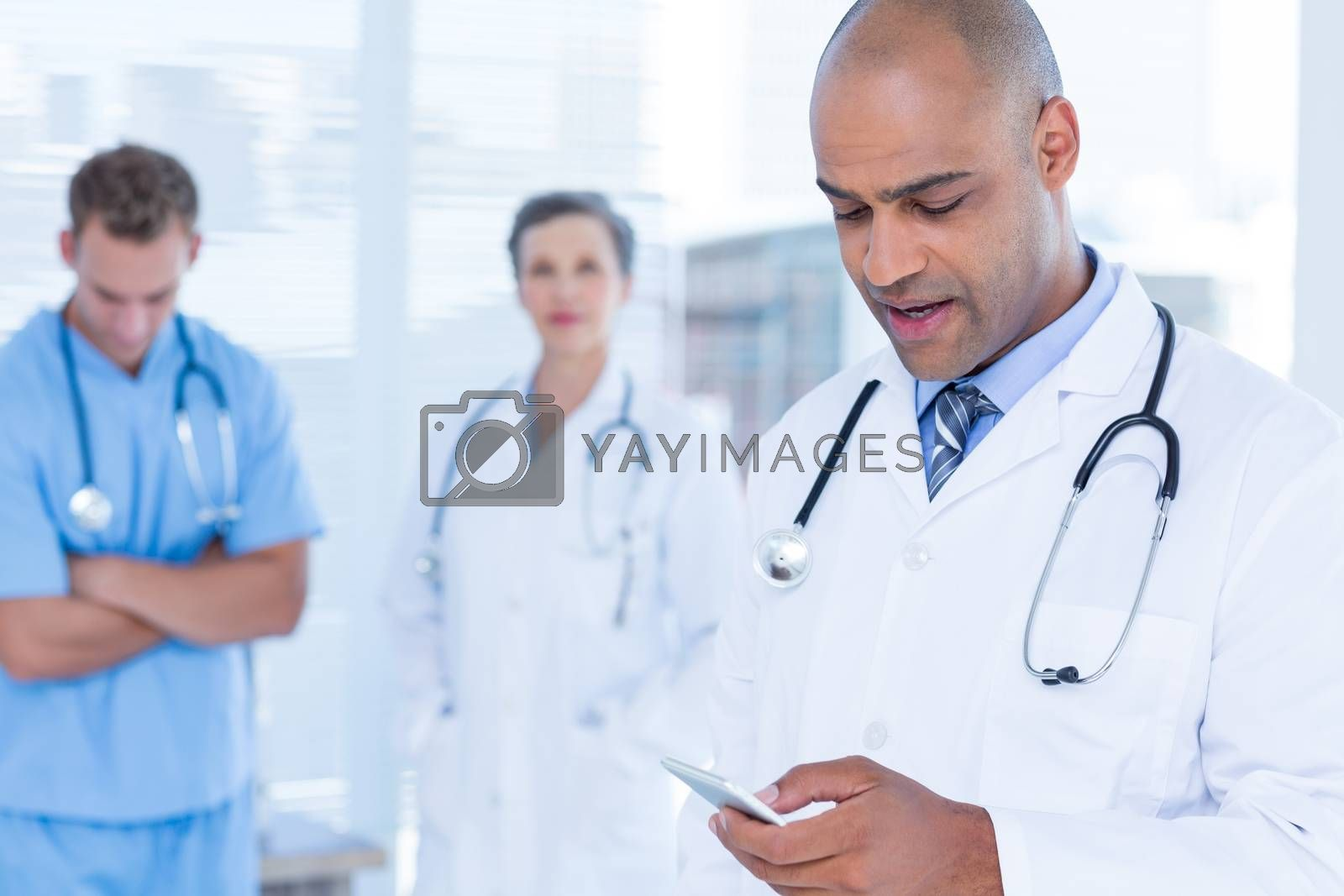 Royalty free image of Attentive doctor sending a text message by Wavebreakmedia