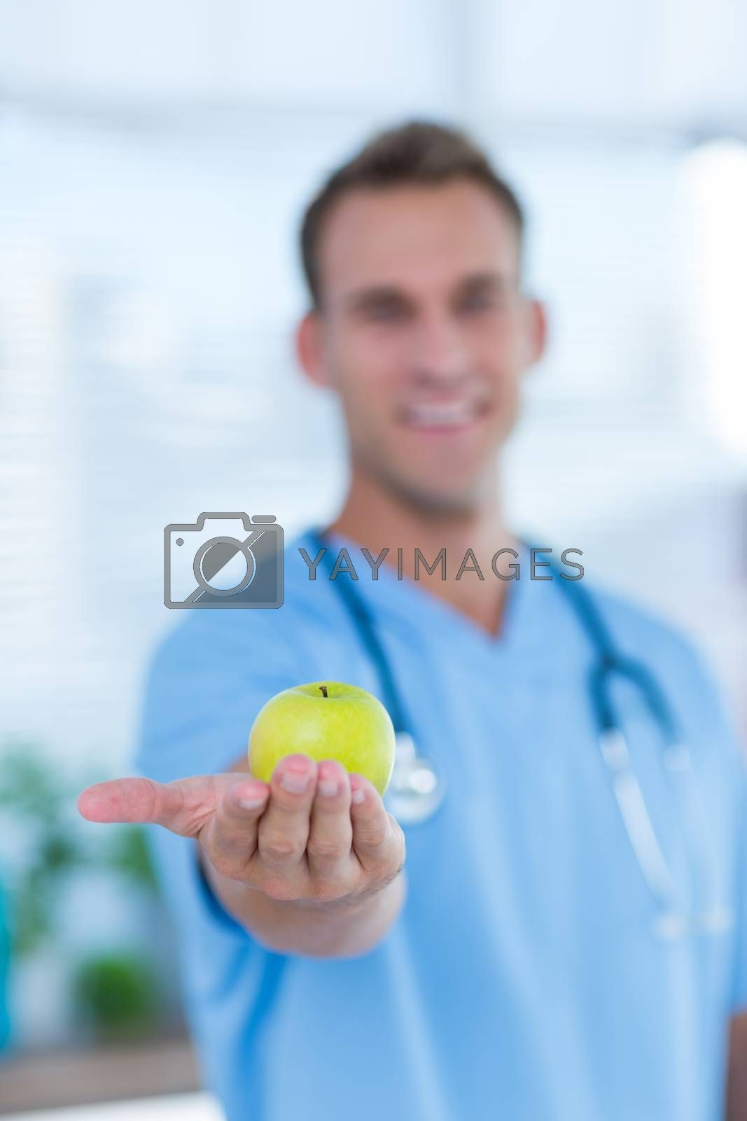 Royalty free image of Smiling doctor presenting a green apple by Wavebreakmedia