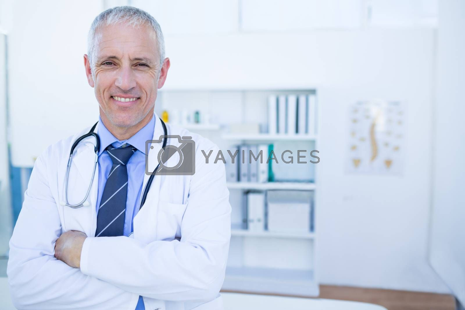 Royalty free image of Happy male doctor looking at camera with arms crossed by Wavebreakmedia
