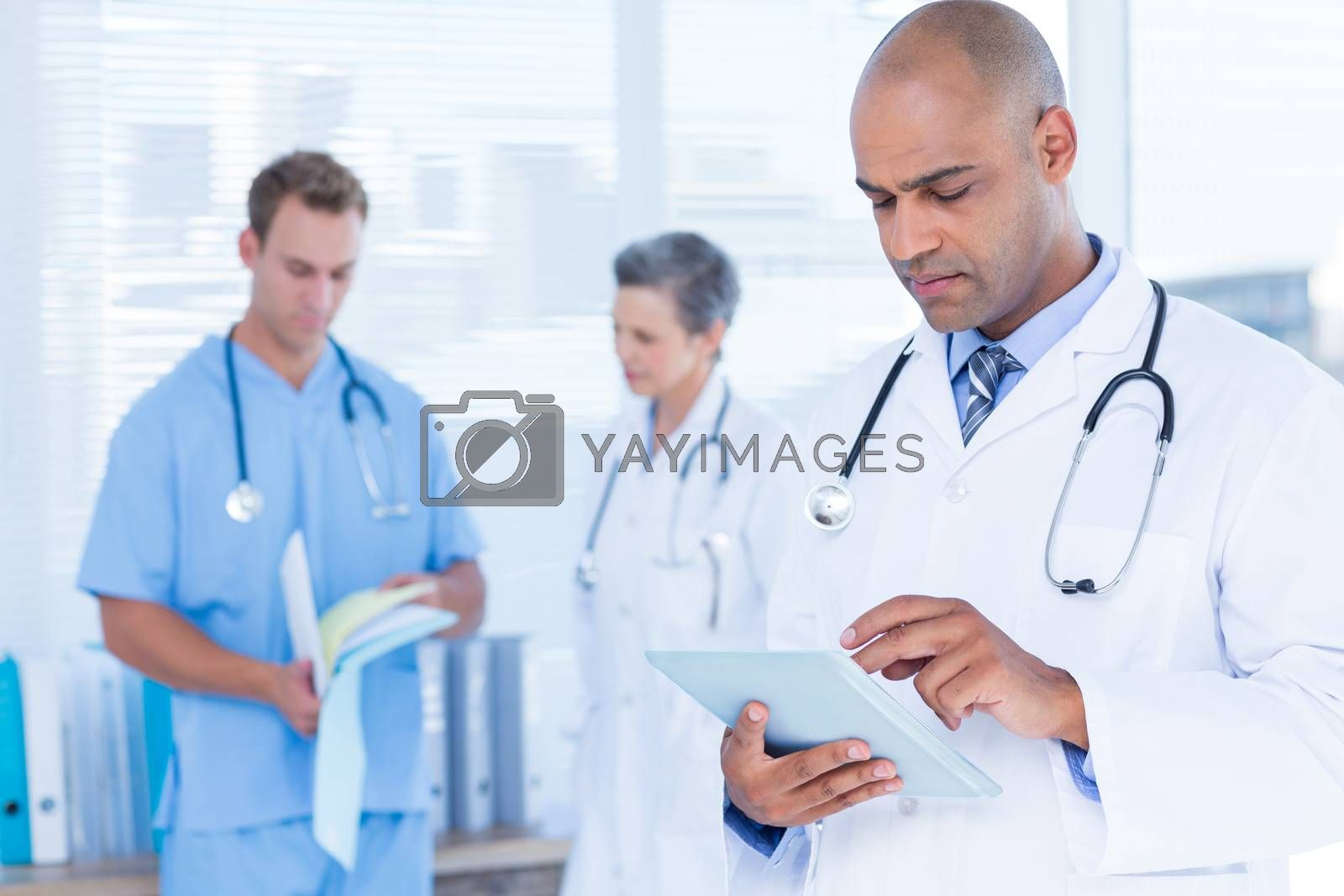 Royalty free image of Attentive doctor using his tablet by Wavebreakmedia